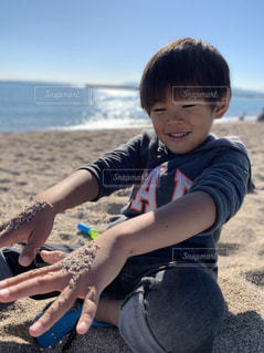 ビーチに座って砂遊びする小さな男の子の写真・画像素材[1595990]