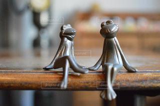 木製テーブルの上に座っているペアのカエルの写真・画像素材[1357815]