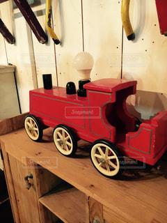 木製テーブルの赤と黒の汽車のおもちゃの写真・画像素材[1383823]