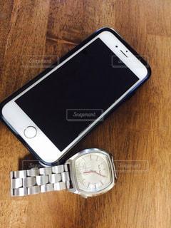 テーブルの上の携帯と腕時計の写真・画像素材[1403911]