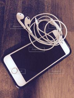 テーブルの上の携帯とイヤホンの写真・画像素材[1403916]