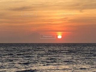 バック グラウンドでサンセット ビーチと水の体の上の日没の写真・画像素材[1334447]