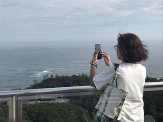海に向かって写真を撮る女性の写真・画像素材[1460740]