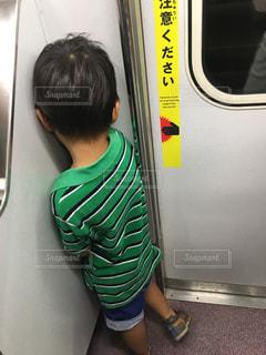 電車の中拗ねてる小さな男の子の写真・画像素材[1337009]