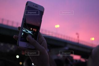 携帯電話で夕焼けを撮影の写真・画像素材[1556444]