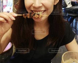 焼き鳥を食べる女性の写真・画像素材[1646646]