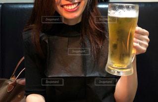 テーブルの上でビールを一杯持っている女性の写真・画像素材[2956485]