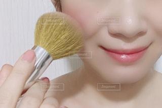 ブラシでチークを塗る女性の写真・画像素材[1378112]