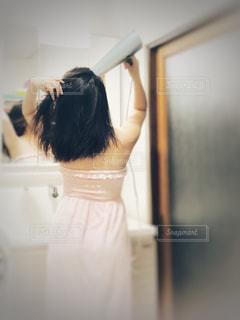鏡の前で髪を乾かす女性。の写真・画像素材[1405412]