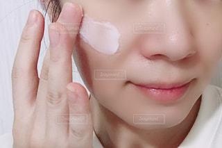 クリームを塗る女性の顔のアップの写真・画像素材[1492329]