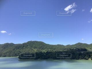 背景に山のある水の体の写真・画像素材[3787411]