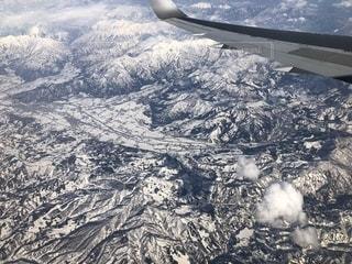 雪の覆われた山上空を飛ぶ飛行機の写真・画像素材[1883413]
