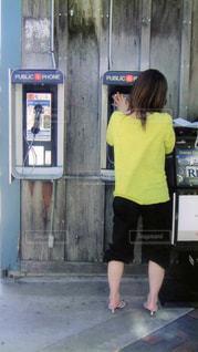 アメリカの公衆電話で電話する女性の写真・画像素材[1386979]