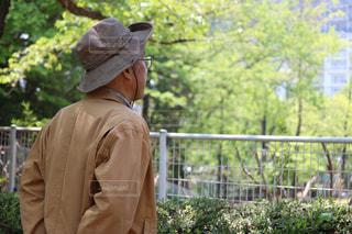 フェンスの前に立っている男の写真・画像素材[1606806]