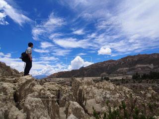 岩が多い丘の上に立っている人の写真・画像素材[1360848]
