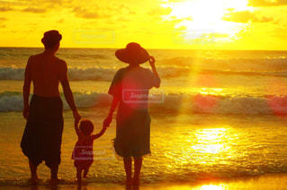 夕陽に染まるビーチと家族の写真・画像素材[1353455]