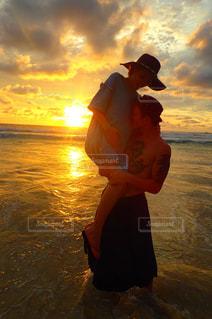 水の体の上に日没の前に立っている人の写真・画像素材[1353504]