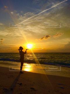 バック グラウンドで夕焼けのビーチに立っている人の写真・画像素材[1353583]