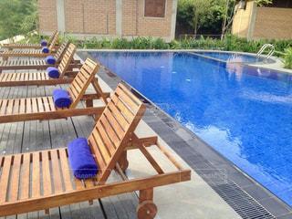 水のプールの横に座っている木製のベンチの写真・画像素材[1359790]