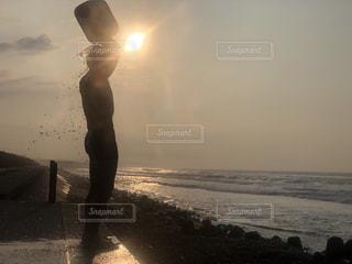 バック グラウンドで夕焼けのビーチに立っている人の写真・画像素材[1367571]
