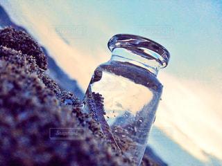 砂浜の小瓶、閉じ込められた羽の写真・画像素材[1366602]