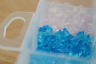 テーブルの上の青いコンテナーにガラスの写真・画像素材[1366680]