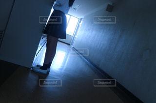 暗い部屋に座っている人の写真・画像素材[1411121]