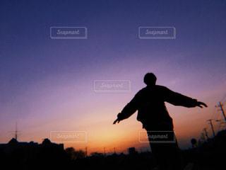 夕焼けの前に立っている男の写真・画像素材[2432436]