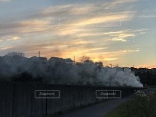野焼きの煙と夕映えの写真・画像素材[1666426]