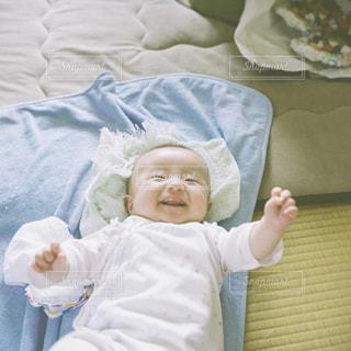 ベッドの上で赤ちゃんを持っている手の写真・画像素材[1458843]