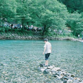 水の体の横に立っている人の写真・画像素材[1564953]