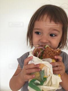 サンドイッチを食べる少女の写真・画像素材[1389638]