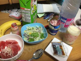 テーブルの上に食べ物のボウル隣のボトルの写真・画像素材[1382535]
