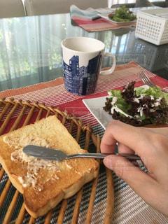 朝食 トーストにバターを塗っての写真・画像素材[1384083]