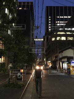 夜の街を歩く男性の後ろ姿の写真・画像素材[2511616]