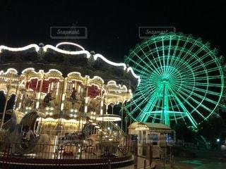 遊園地のライトアップされたメリーゴーランドと観覧車です。の写真・画像素材[1426791]