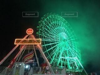 遊園地のライトアップされた遊具と観覧車です。花火大会終わりの煙が写っています。の写真・画像素材[1427037]