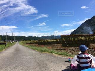 道の端に座っている少年の写真・画像素材[1429434]