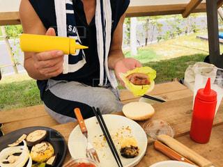 食品のプレートをテーブルに座っている男性の写真・画像素材[1456544]