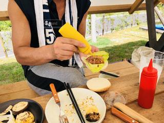 食品のプレートをテーブルに座っている男性の写真・画像素材[1456545]