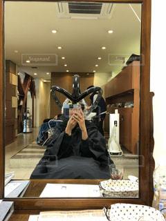 カメラにポーズ鏡の前に立っている人の写真・画像素材[1636834]