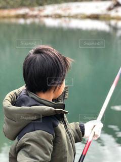 水域の隣に立っている少年の写真・画像素材[2897396]