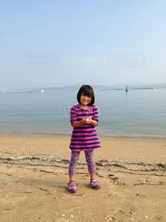 浜辺の前に立つ小さな女の子の写真・画像素材[2422559]
