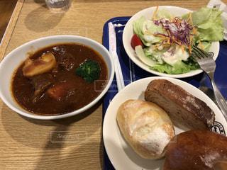 テーブルの上の皿の上に食べ物のボウルの写真・画像素材[1401116]