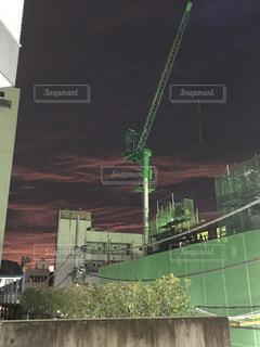 近くに緑の建物の工事現場のクレーンの写真・画像素材[1401549]