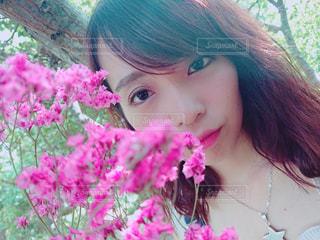 近くにピンクの花の女性のアップの写真・画像素材[1403384]