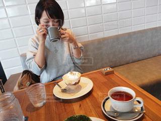 一杯のコーヒーをテーブルに座っている女性の写真・画像素材[1632708]