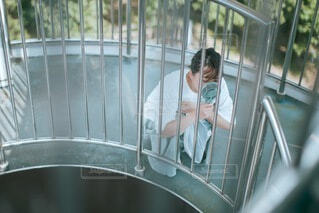 金属製のフェンスの上に座っている人の写真・画像素材[3620928]
