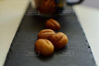 近くに木製のまな板の上に座っているドーナツのアップの写真・画像素材[1709285]