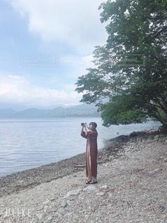 水域の隣に立っている人の写真・画像素材[2380653]